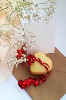 Biscotti a forma di cuore con un nastro rosso e un mazzo di fiori bianchi. spazio per il testo.