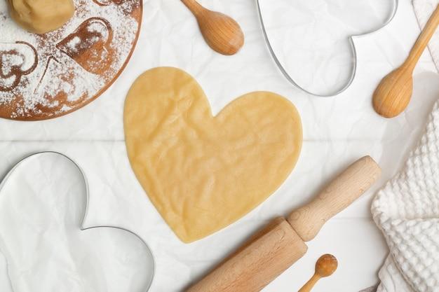 Uno stampo da ritagliare a forma di cuore sulla pasta arrotolata accanto a un asciugamano e cucchiai di legno e mattarello, adagiati.