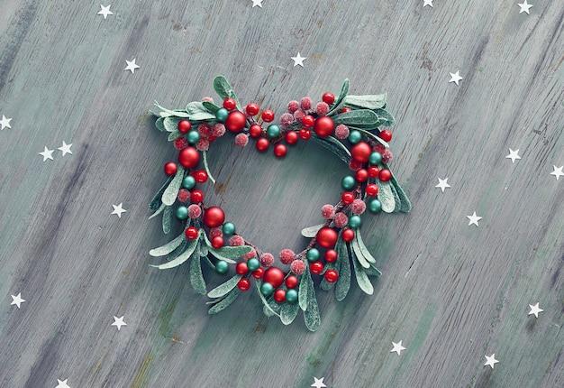 Corona decorativa di vischio di natale a forma di cuore con bacche rosse e foglie verdi.