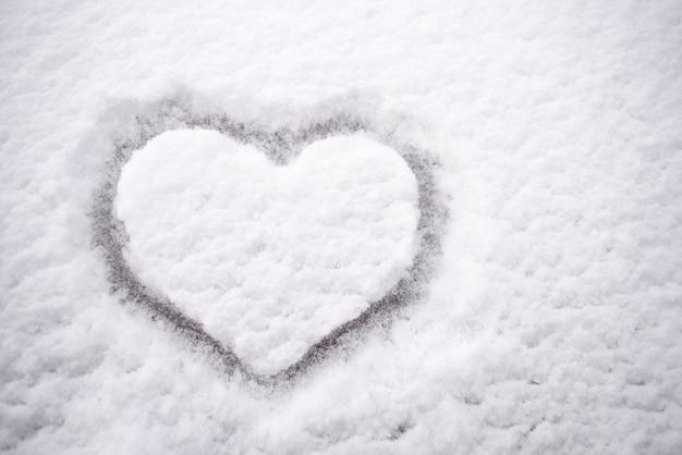 Disegno sul bianco della neve a forma di cuore