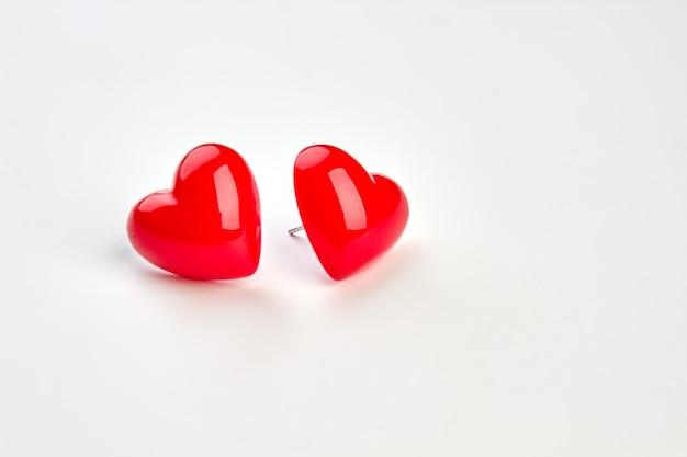 Orecchini a forma di cuore su sfondo bianco. coppia di due piccoli cuori rossi per san valentino, copia spazio. bellissimo accessorio femminile.