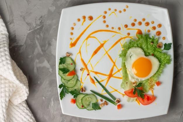 Uovo fritto a forma di cuore con verdure, erbe e salsa sul piatto quadrato bianco su una superficie di cemento grigio