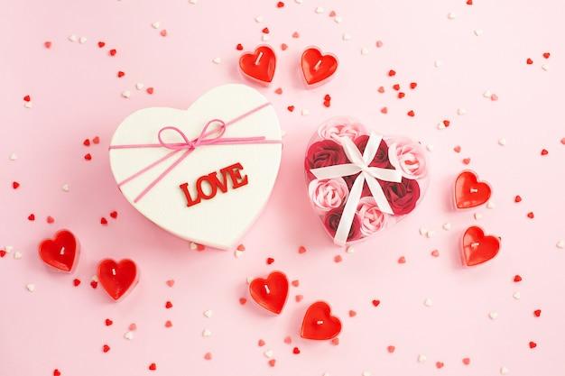 Scatola regalo a forma di cuore, regalo, candela, coriandoli sul rosa.