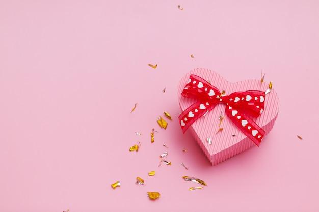 Scatola regalo a forma di cuore su sfondo rosa con particelle di scintillio festivo volanti