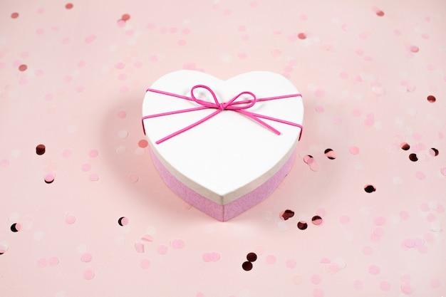 Scatola regalo a forma di cuore con fiocco rosa e coriandoli, vista dall'alto