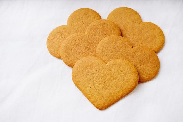 Biscotti di panpepato a forma di cuore su una superficie tessile bianca.