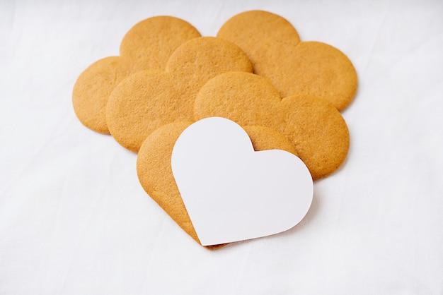 Biscotti di panpepato a forma di cuore con una carta bianca su una superficie tessile bianca.