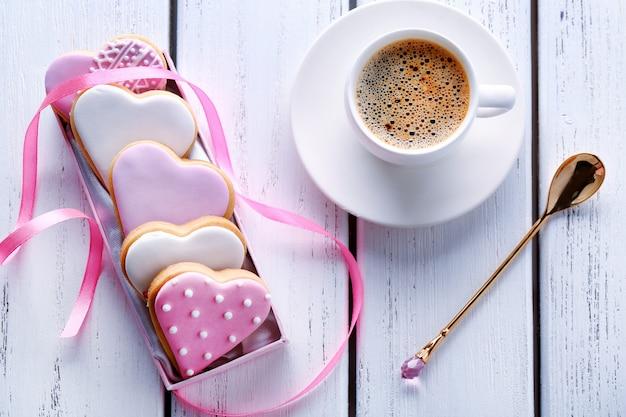 Biscotti smaltati a forma di cuore e tazza di caffè su fondo di legno
