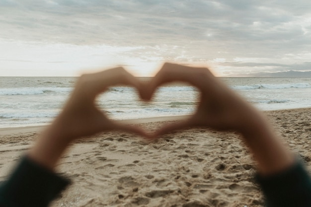 Mano a forma di cuore sulla spiaggia