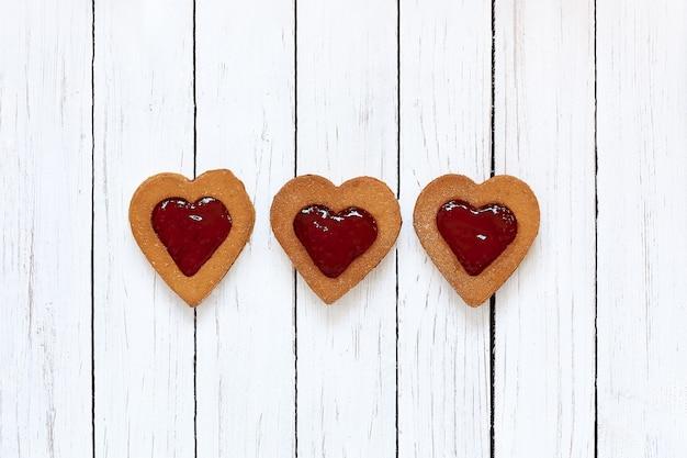 Biscotti fatti in casa a forma di cuore con marmellata di fragole su fondo di legno bianco. compleanno, san valentino, festa della mamma. vista dall'alto. biscotti di farina senza glutine