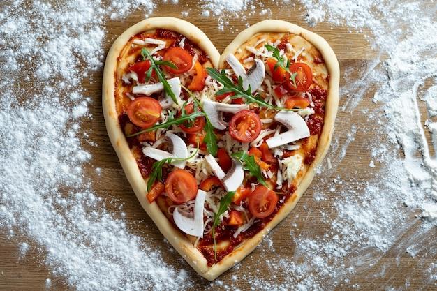 La pizza italiana a forma di cuore per alimenti dietetici si trova in una pizzeria su un tavolo cosparso di farina per il giorno di san valentino. ordine individuale con paperroni, funghi, pomodori e rucola.