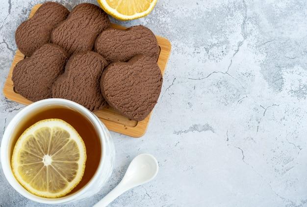 Tè al limone a forma di cuore e biscotti con gocce di cioccolato, posto per il testo