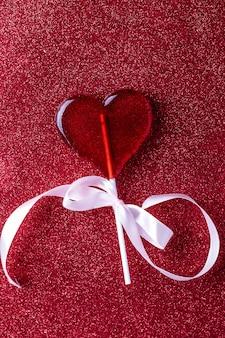Lecca-lecca a forma di cuore su sfondo rosso. sfondo di san valentino copia spazio