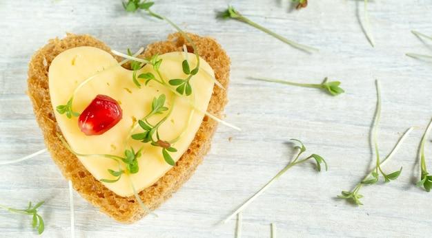 Mini tartine a forma di cuore con burro, formaggio e micro verdi di crescione su un tavolo di legno bianco. vista dall'alto.