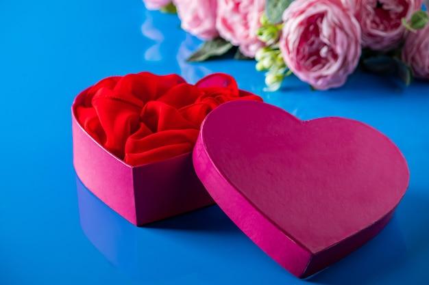 Contenitore di regalo aperto a forma di cuore sull'azzurro