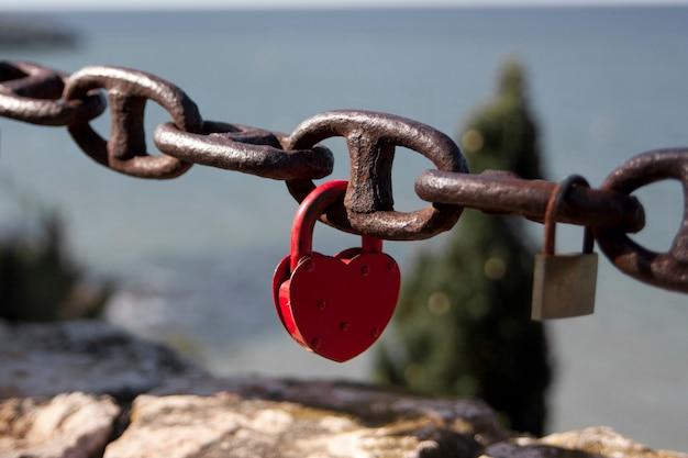 Lucchetto a forma di cuore sulla catena in riva al mare concetto di amore eterno