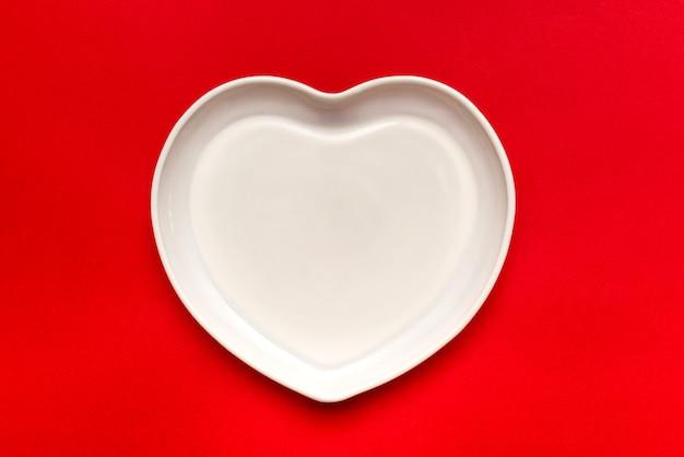 Piatto a forma di cuore. stoviglie in ceramica. su sfondo rosso. con un'ombra dura.