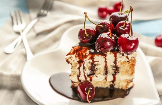 Piatto a forma di cuore con un pezzo di deliziosa torta di ciliegie sul tavolo