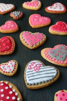 Biscotti di glassa reale a forma di cuore sparsi su fondo di legno marrone scuro