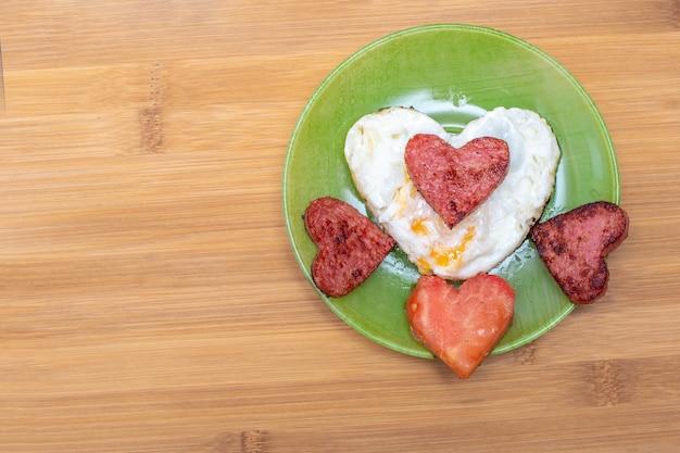 Uova strapazzate a forma di cuore con salsicce e pomodoro a forma di cuore su un piatto verde su sfondo di bambù, vista dall'alto, spazio copia. colazione per i propri cari a san valentino