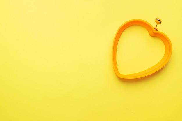 Stampo in silicone a forma di cuore per cuocere e friggere uova su fondo giallo. vista dall'alto, minimalista, copia spazio.