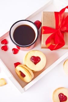 Biscotti linzer tradizionali a forma di cuore con marmellata di fragole, tazza di caffè e confezione regalo