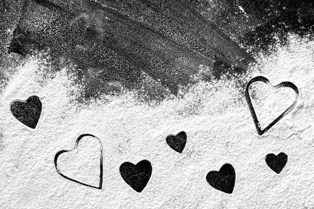 Forme di cuore di diverse dimensioni fatte di farina sul bordo scuro
