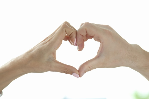 Segno del cuore fatto dalle mani. la mano maschile e femminile insieme raffigura il cuore