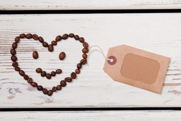 Faccina sorridente del cuore fatta di chicchi di caffè e tag vuoto. posto per copyspace. fondo di legno bianco.