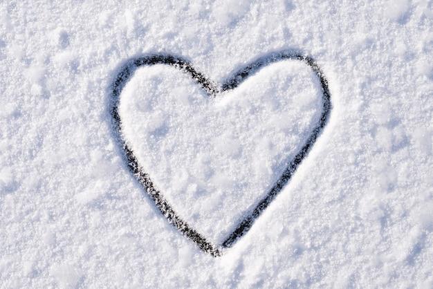 Cuore sulla neve disegnato con un dito indice