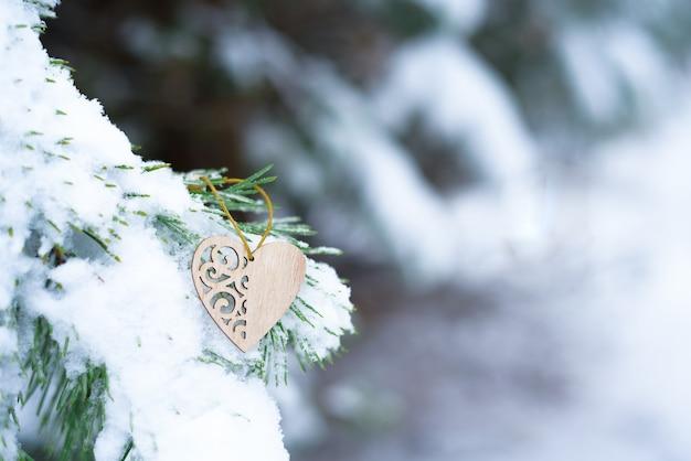Cuore sulla neve sui rami di abete in inverno, concetto di sfondo vacanza di san valentino.