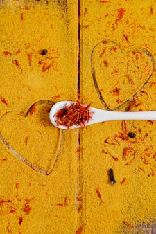 Cuore di spezie e condimenti. cucchiaio bianco con zafferano su sfondo di curry. selezione di spezie varie. avvicinamento. copia spazio. amore