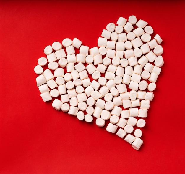Simbolo del cuore fatto da marshmallow su sfondo rosso. vista dall'alto. lay piatto
