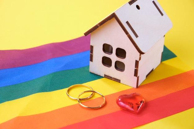 Cuore, fedi nuziali e una piccola casa di legno sulla bandiera lgbt, sfondo giallo, luogo di copia