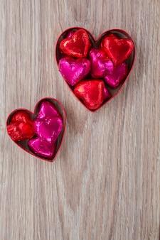 Cuore con caramelle sulla tavola di legno