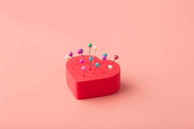 Cuore con aghi su uno sfondo colorato. amore infelice
