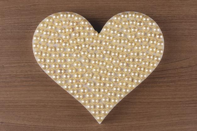 Cuore con perle su fondo in legno.