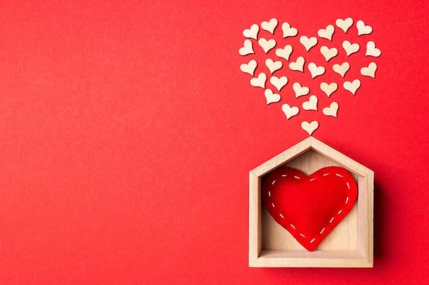 Cuore sulla casa in legno con un sacco di cuori in legno sul rosso. lay piatto