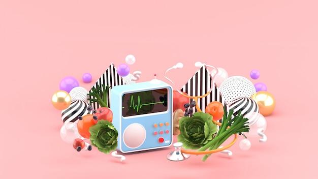 Misuratore di battito cardiaco e stetoscopio tra un alimento sano e palline colorate su uno spazio rosa