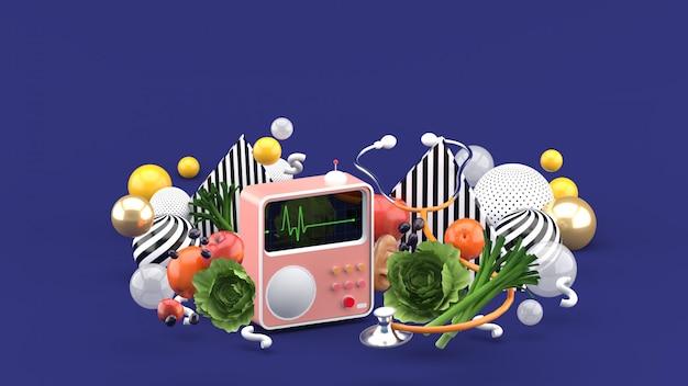 Misuratore di battito cardiaco e stetoscopio tra un alimento sano e palline colorate su uno spazio viola