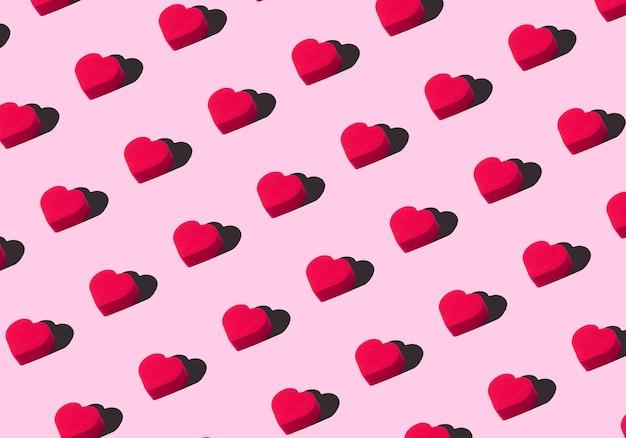 Sfondo di cuori. ornamento colorato da ritagliare cuori rossi su sfondo rosa. amore, romanticismo, carta da parati, concetto minimo di cartolina