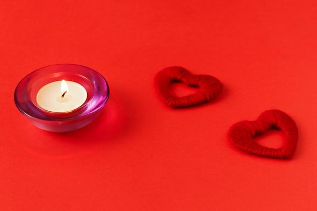 Cuori e candela su uno sfondo rosso