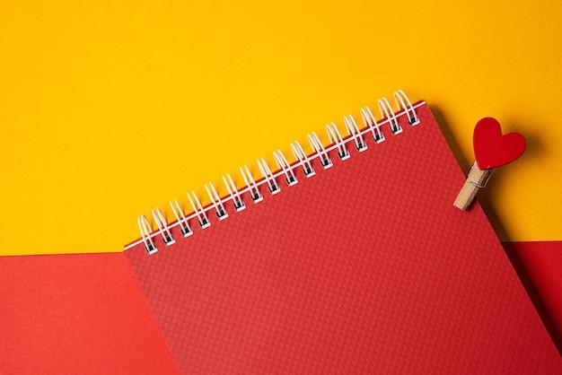 Cuori su una molletta da bucato su carta rossa