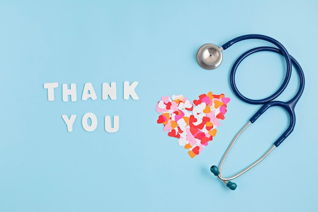 Coriandoli di cuori e testo grazie. esprimendo gratitudine all'idea di medici e infermieri