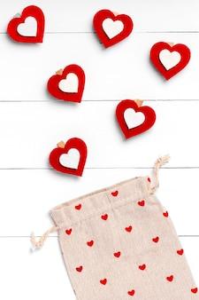 Cuori ed ecobag su superficie di legno bianca. concetto di san valentino. vista piana, vista dall'alto, dall'alto