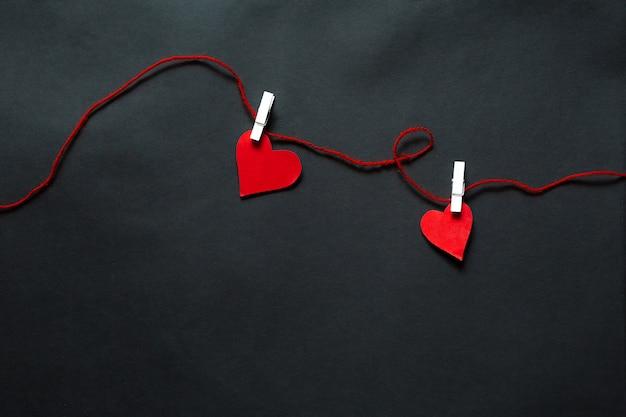 Cuori appesi su spago su uno sfondo nero. sfondo di san valentino