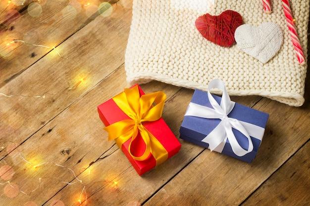 Cuori, sciarpa lavorata a maglia, scatole regalo, ghirlanda luminosa su fondo in legno. concetto di innamorati, san valentino, un regalo per una persona cara.