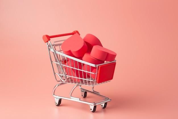 Cuori nel carrello della spesa e nel carrello del supermercato su sfondo colorato. sfondo per san valentino (14 febbraio) e amore.