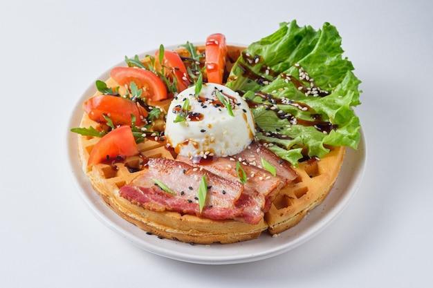 Sostanziosi waffle belgi con uova in camicia pancetta lattuga pomodoro e rucola con semi di sesamo