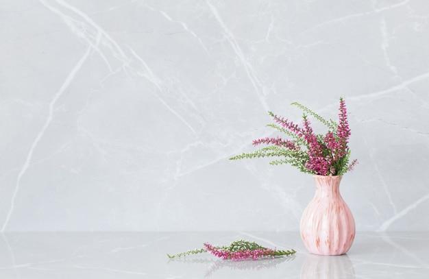 Bouquet di erica in vaso su sfondo di marmo grigio